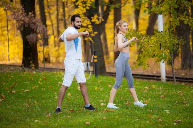 パーソナルトレーナーは、女性が屋外で運動しながらメモを取る