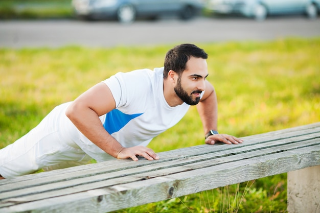 公園でのフィットネス。スポーツウェアで屋外トレーニング若くてスポーティな男。スポーツ、健康、運動。