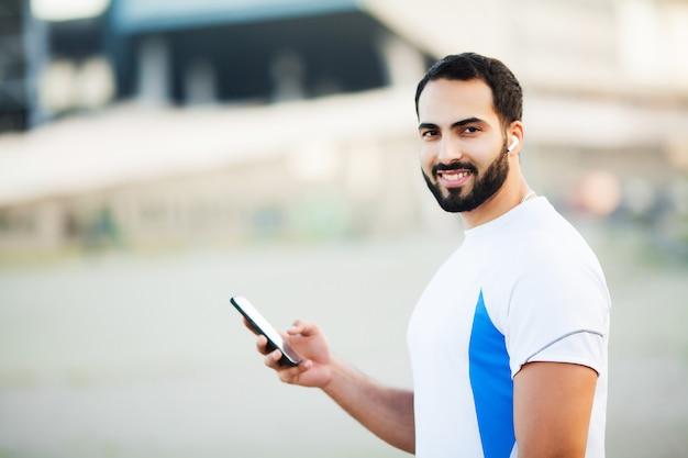 Человек после тренировки в городском парке и с помощью своего мобильного телефона
