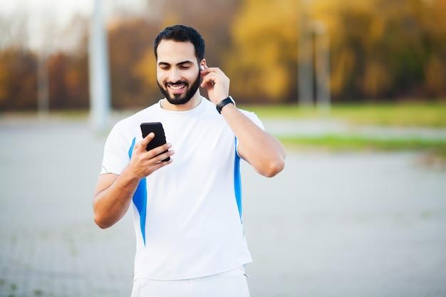 都市公園でワークアウトし、彼の携帯電話を使用した後の男
