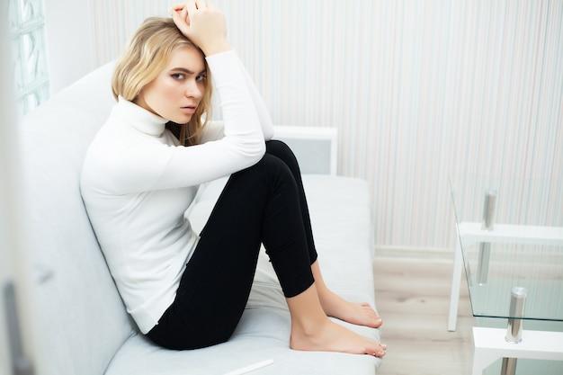 妊娠検査陽性。妊娠検査棒を保持している絶望的な若い女性の肖像画