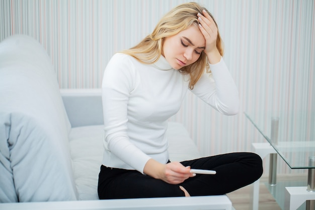 Положительный тест на беременность. портрет отчаянной молодой женщины, держащей палку теста на беременность