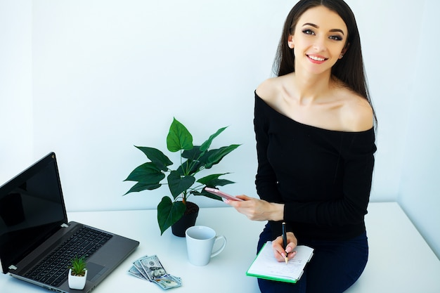 オフィスビジネス女性の笑みを浮かべて、テーブルの上に座っています。