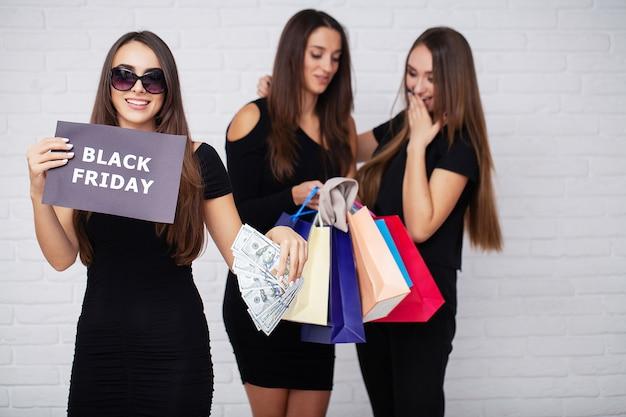 ショッピング。エレガントなブルネットの女性は、買い物袋、黒い金曜日の概念を保持している黒いドレスを着ています