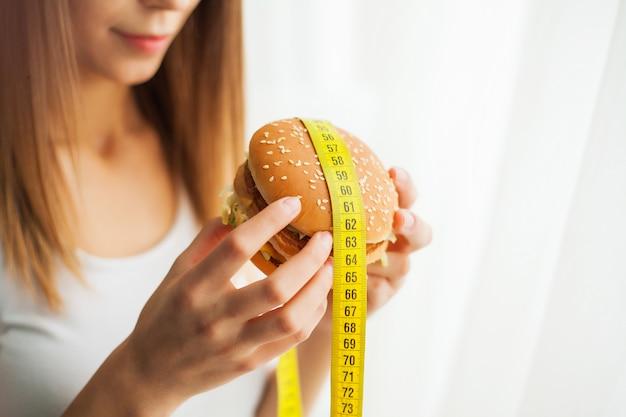 ダイエット。ジャンクフードを食べる彼女を防ぐ若い女性。健康的な食事のコンセプト