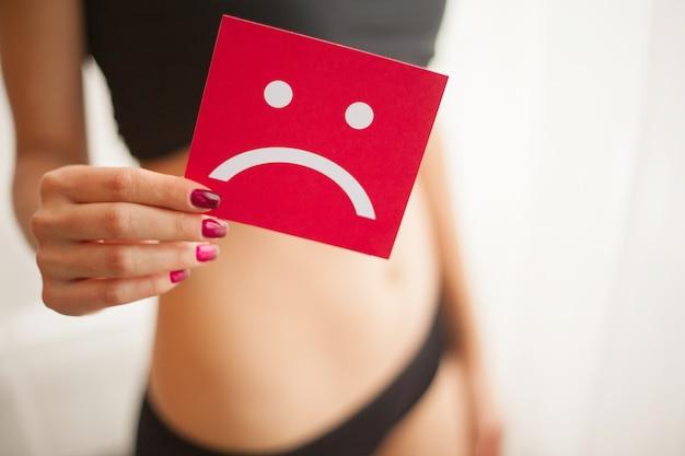 女性の健康。胃の近くの悲しい笑顔カードを保持している女性の身体