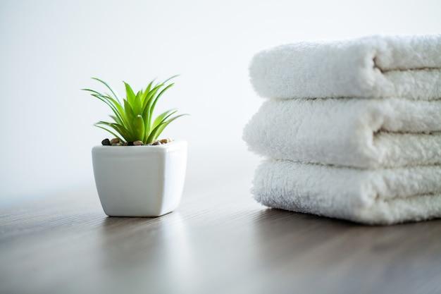 スパ。スパのバスルームで使用する白い綿のタオル。タオルのコンセプト。ホテルおよびマッサージ店の写真。純度と柔らかさ。タオルテキスタイル