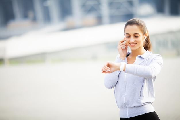 スポーツ女性の演習を行い、都市環境で音楽を聴く