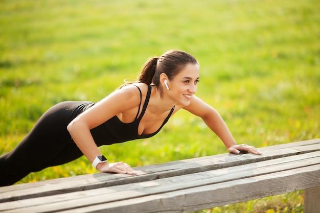 フィットネス、日没、屋外スポーツ、レクリエーションおよび動機の概念で板の位置に立っている運動の女性