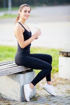 フィットネス女の子、公園でスポーツウェア飲料水で若い美しい女性