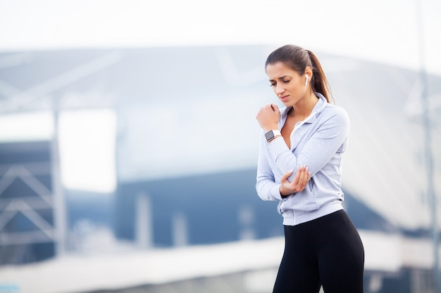 フィットネス、女性は、屋外、筋肉痛の概念でのトレーニング中に事故で負傷し、腕を傷つける