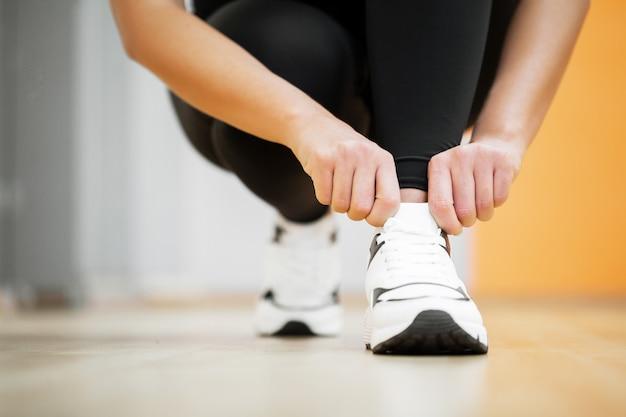 Фитнес женщина связывает кроссовки веревкой, спортивной одеждой и темой моды