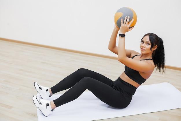 Женщина фитнеса делая тренировки на взгляд сверху прессы, милая разминка девушки в спортзале