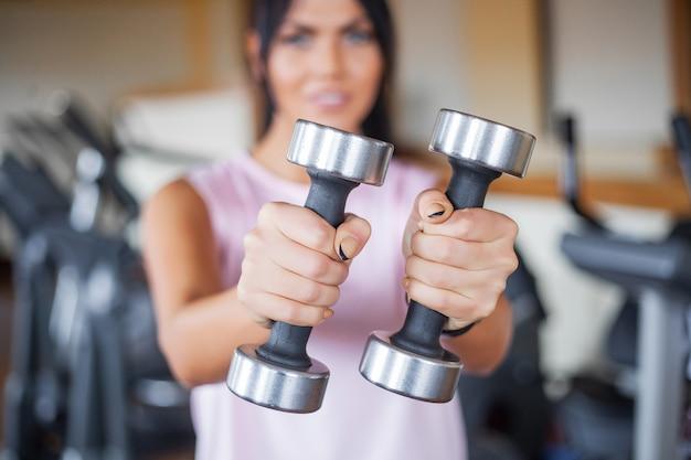 ダンベルを持つ若い女性がジムで運動をする
