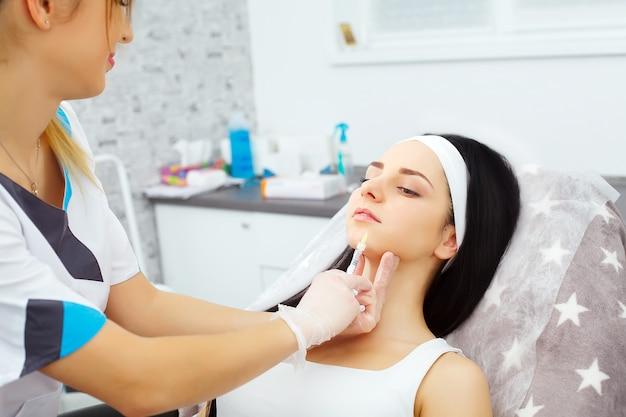 Довольно кавказских женщин, имеющих инъекции гиалуроновой кислоты в зону лица. мужской доктор с шприц, заполняя лицо женщины с коллагеном. концепция омоложения терапии.
