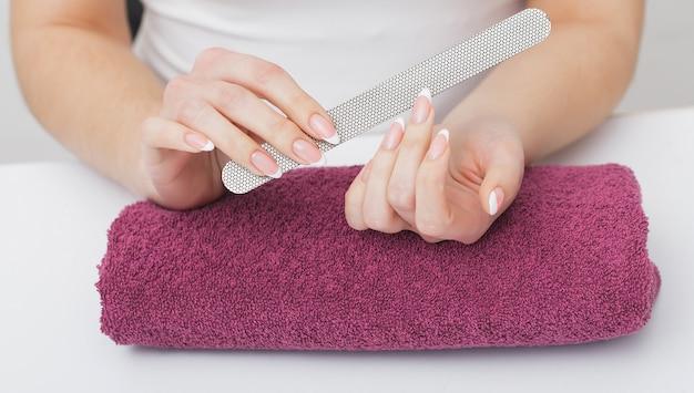 女性の手のケア。ビューティーサロンでスパマニキュアを持つ美しい女性の手のクローズアップ。美容師ファイリングクライアントネイルファイルと健康的な自然な爪。ネイルトリートメント。高解像度