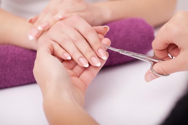 ネイルケアとマニキュア。ビューティーサロンで健康的な自然な女性の爪に透明なマニキュアを適用する美しい女性の手のクローズアップ。ネイリストハンドペインティングクライアントの爪。高解像度