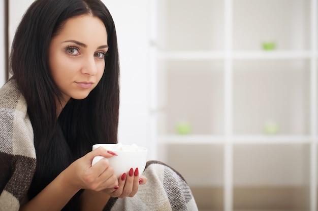 ベッドで病気の女性、病気で呼び出し、仕事から休みます。ハーブティーを飲む。インフルエンザのためのビタミンと熱いお茶。女性は風邪をひいた。ウイルス。赤痢。下痢。病気と疲れている女性