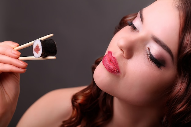 Девочка ест суши с палочками для еды