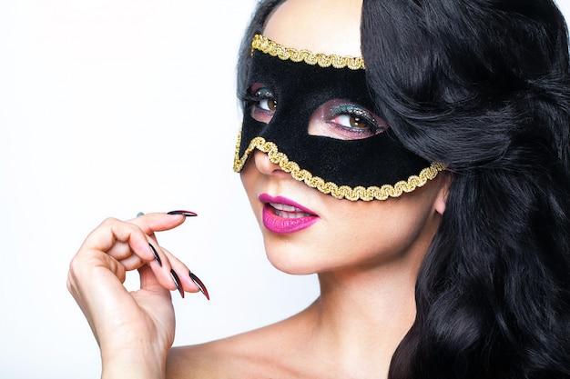 ヴェネツィアマスクスタジオポートレートを持つ魅力的な若い女性。