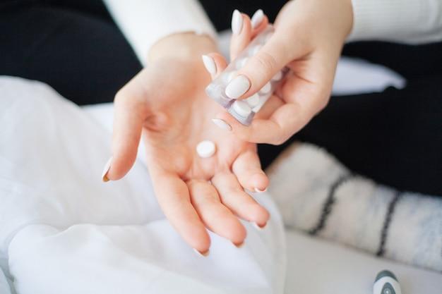 医療薬、ブリスターから錠剤を抽出する女性