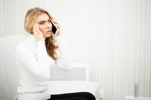 Головная боль, женщины сидят на кровати, держась за голову, у нее болит головная боль