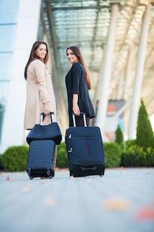 Отпуск, две счастливые девушки путешествуют вместе за границей, неся чемодан в аэропорту