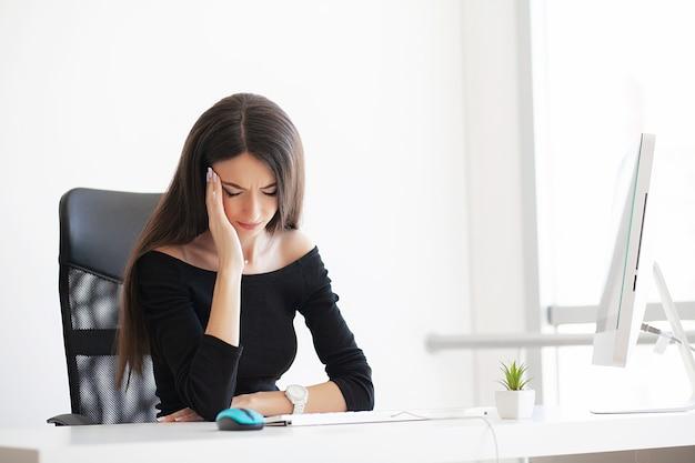 美しい少女はオフィスのテーブルに座って、彼女の頭の近くに彼女の手を握っています。