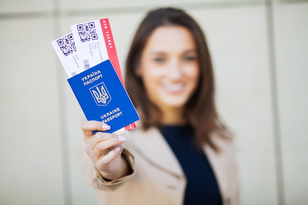 Путешествие, женщина держит два авиабилета в заграничном паспорте возле аэропорта