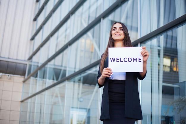 旅行、歓迎メッセージ付きポスター付き女性ビジネス