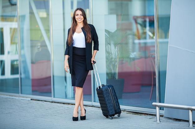 Путешествие, молодая женщина идет в аэропорту у окна с чемоданом в ожидании самолета