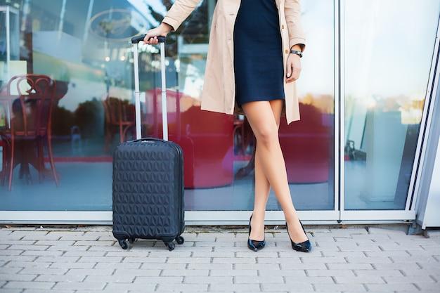 屋外の都市の道路でスーツケースと夏のカジュアルな服で足を組んで画像旅行者観光女性をトリミング