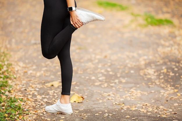 公園でストレッチ運動を行うフィットネス女性