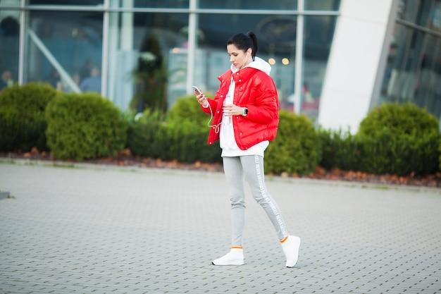 フィットネス女の子。近代的な都市でストレッチ若いスポーツ女性。大都市の健康的なライフスタイル