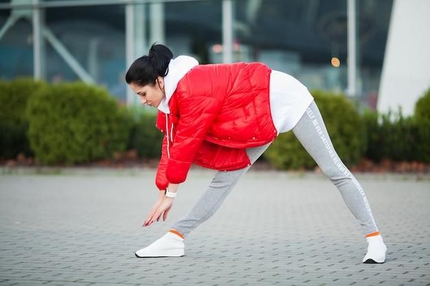 体を伸ばして、通りで運動をしている女性