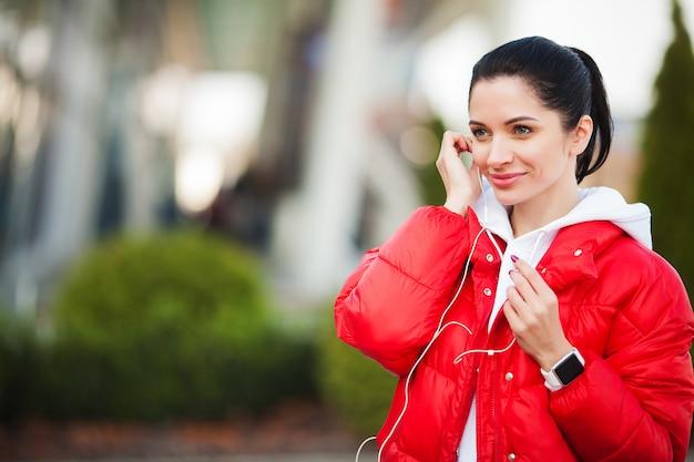 フィットネス女の子。実行して、屋外の音楽を聞いてかなりスポーティな女の子。大都市の健康的なライフスタイル