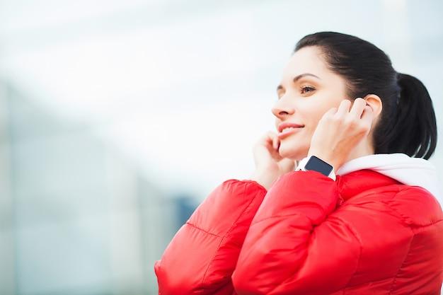 フィットネス女性。空港近くのイヤホンでスポーツウェアの若い女性