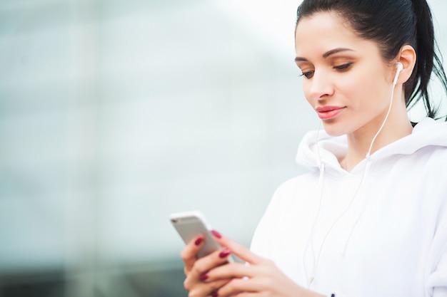 フィットネス。屋外-スポーツと健康的なライフスタイルのコンセプトを行使しながら携帯電話で音楽を聴く女性