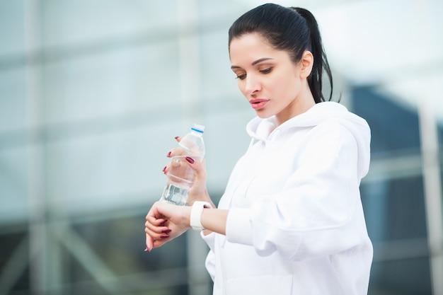 屋外フィットネス。水のボトルを飲む女性