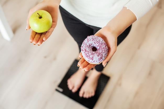 Рацион питания. женщина, измерения веса тела на весах холдинг пончик и яблоко. сладости нездоровая нездоровая пища. быстрое питание