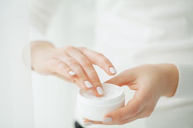 ハンドスキンケア。クリームチューブ、柔らかい絹のような健康的な肌に化粧品のハンドクリームを適用する自然なマニキュアの爪を持つ美しい女性の手を保持している女性の手のクローズアップ