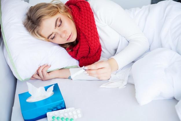 病気の女性。ベッドに横たわっているインフルエンザウイルスを持つ女性、彼女は温度計で彼女の温度を測定しています
