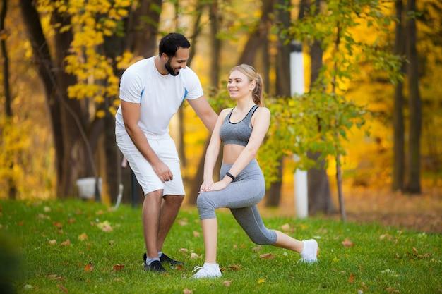 フィットネス。パーソナルトレーナーは、女性が屋外で運動しながらメモを取る