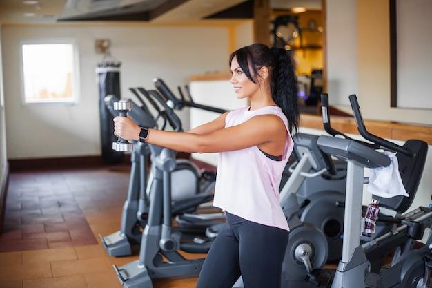 スポーツと健康的なライフスタイルのコンセプト。ダンベルを持つ若い女性がジムで運動をする