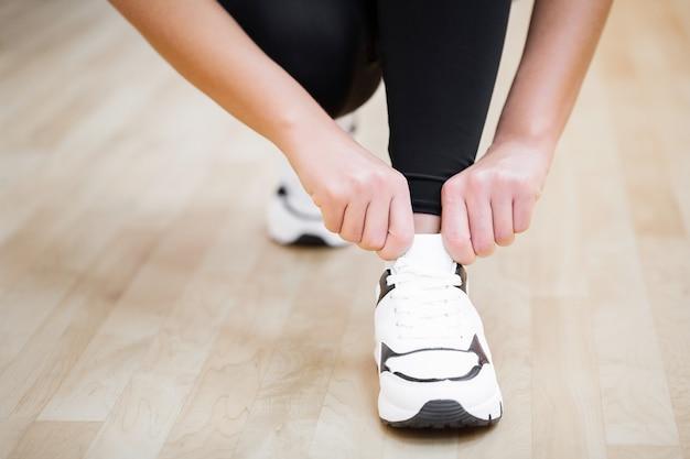 Физическая активность. крупным планом девушки, связывая шнурки на спортивной обуви в тренажерном зале