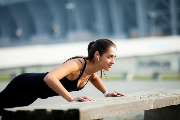 フィットネス。完璧な筋肉を持つ美しい少女。彼女は背中の筋肉を鍛えます。コンセプト-パワービューティーダイエットスポーツ