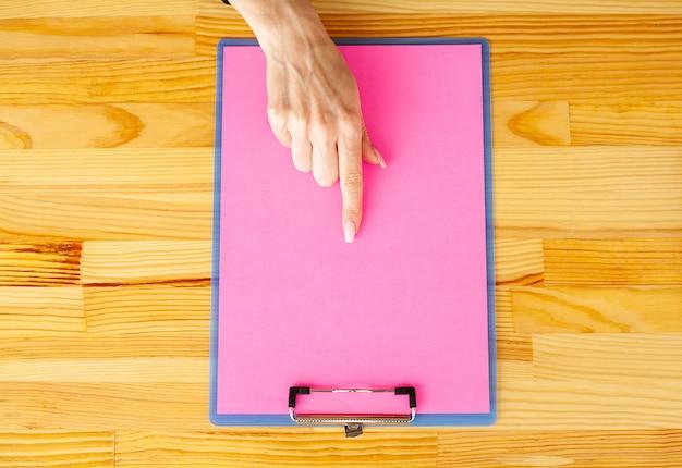 ピンクの紙で空白のフォルダー。フォルダーとハンドルを持っている手