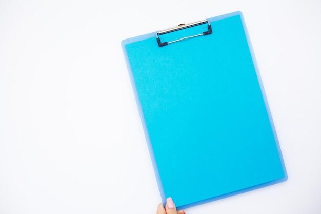 青い紙の空のフォルダー。白い背景の上にフォルダーとペンを保持している手。コピースペース。