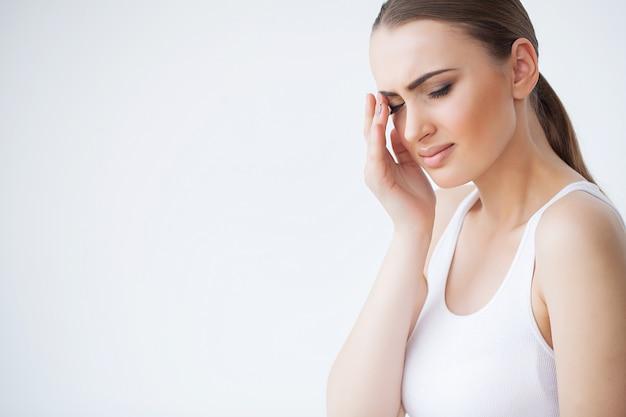 健康と頭痛。痛みを感じて、強い頭痛を持つ美しい女性