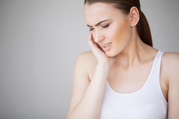 歯痛。歯の痛みを感じる女性。強い歯の痛みに苦しんでいる美しい悲しい少女のクローズアップ。魅力的な女性の痛みを伴う歯痛。歯の健康とケアのコンセプト